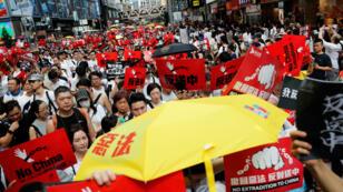 Des manifestants portant des parapluies jaunes, en référence au mouvement Occupy Central, lors de la manifestation à Hong Kong, le 9 juin 2019.