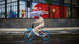 File photo of a woman cycling past an image of the Chinese flag after the lockdown was lifted in Wuhan April 10, 2020.