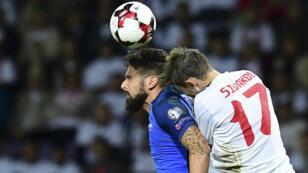 Le Français Olivier Giroud (à gauche) et le Biélorusse Mikhail Sivakow se disputent le ballon lors du premier match de qualification pour le Mondial-2018 mardi à Borisov.