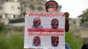 """سيدة تحمل صورة لأربع من فتيات شيبوك كتب عليها """"أعيدوا بناتنا"""" في 14 تشرين الأول/أكتوبر 2014"""