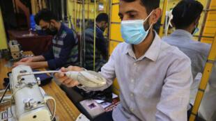 عمال من بنغلادش وباكستان في معمل للخياطة في حي الكرادة في بغداد في 23 حزيران/يونيو 2020