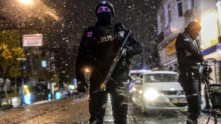 A police officer stands guard under the snow along a street leading to a police station where a female suicide bomber blew herself up on January 6, 2015, also killing a policeman