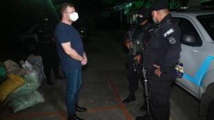 El ex ministro de Defensa salvadoreño David Munguia Payes (I) esposado después de que el Ministerio Público ordenara su captura por presuntos delitos, el 23 de julio de 2020 en San Salvador