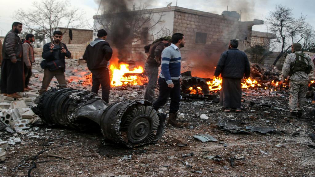 Personas caminan entre los escombros del avión ruso Su-25 que fue derribado por los rebeldes sirios en la provincia de Idlib el 3 de febrero de 2018.