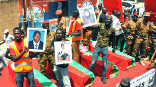 Le 9 octobre 2015, des Burkinabè brandissent des portraits de victimes du pustch manqué.