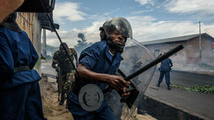 A Burundian police officer holding a baton and army forces run after protestors throwing stones during a demonstration against incumbent president Pierre Nkurunziza's bid for a third term on May 13, 2015 in Bujumbura