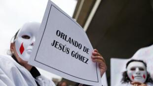 """Un familiar de una víctima de """"falsos positivos"""" sostiene un cartel con el nombre de uno de los fallecidos durante una protesta contra el ex comandante colombiano Mario Montoya fuera de la Jurisdicción Especial para la Paz (JEP) en Bogotá, Colombia, 13 de septiembre de 2018."""