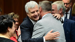 Le ministre de l'Environnement italien Gian Luca Galletti (de face) embrasse son homogue polonais Jan Szyszko à l'issue d'une réunion extraordinaire des ministres européens de l'Environnement à Bruxelles le 30 septembre 2016.