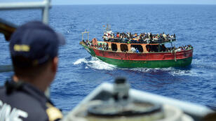Un membre de la marine française près d'un bateau de migrants, au large de l'Italie, le 20 mai 2015.