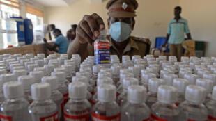 Un policía empaqueta las botellas de desinfectantes en Chennai, India, el 23 de abril de 2021