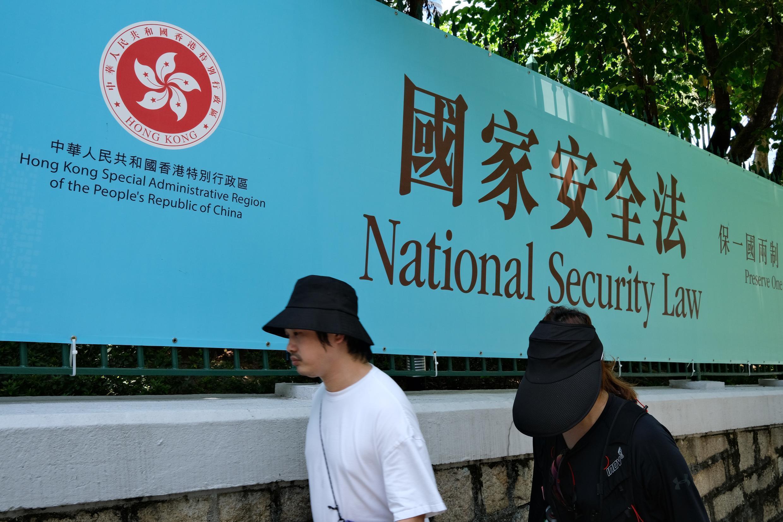 Des piétons devant une bannière publique d'avis du gouvernement pour la loi sur la sécurité nationale à Hong Kong le 15 juillet 2020.