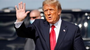 Former US President Donald Trump waves as he arrives at Palm Beach International Airport in Florida on January 20, 2021.