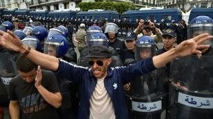 Algerian security forces stand guard behind protesters in the capital Algiers on Friday