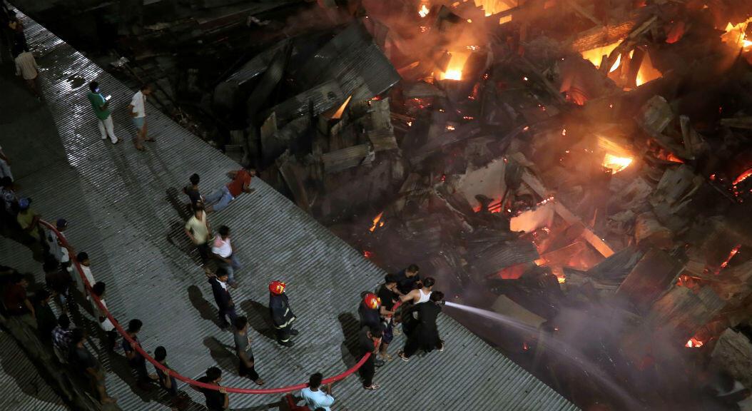 Un grupo de bomberos intenta extinguir un incendio que se produjo en un barrio de bajos recursos, a las afueras de Dacca, Bangladesh, el 16 de agosto de 2019.