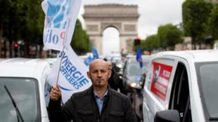 ضابط بوليس فرنسي يتظاهر على جادة الشانزليزيه احتجاجا على منع أسلوب تقييد الرقبة لاحتجاز المشتبه بهم. الجمعة 12 يونيو/حزيران 2020.