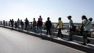 """Los migrantes centroamericanos de la caravana """" Viacrucis Migrante"""" caminan hacia una reunión de asesoramiento legal en Tijuana, en el estado mexicano de Baja California, antes de su entrada a Estados Unidos. 28 de abril de 2018."""