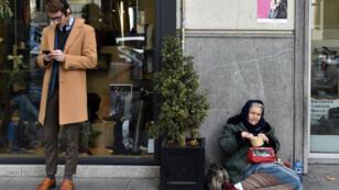 Un homme regarde son téléphone portable à côté d'une femme mendiant sur le trottoir à Madrid, le 15 décembre 2015.