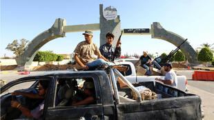 """Des miliciens de la coalition """"Fajr Libya"""" devant l'entrée de l'aéroport de Tripoli, dimanche 24 août.."""