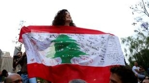 Independent parliamentary candidate Joumana Haddad holds a Lebanese flag in front of the interior ministry in Beirut, on May 7, 2018