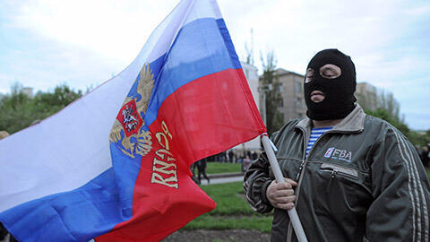 A pro-Russia separatist in the eastern Ukrainian region of Donetsk holds a Russian flag