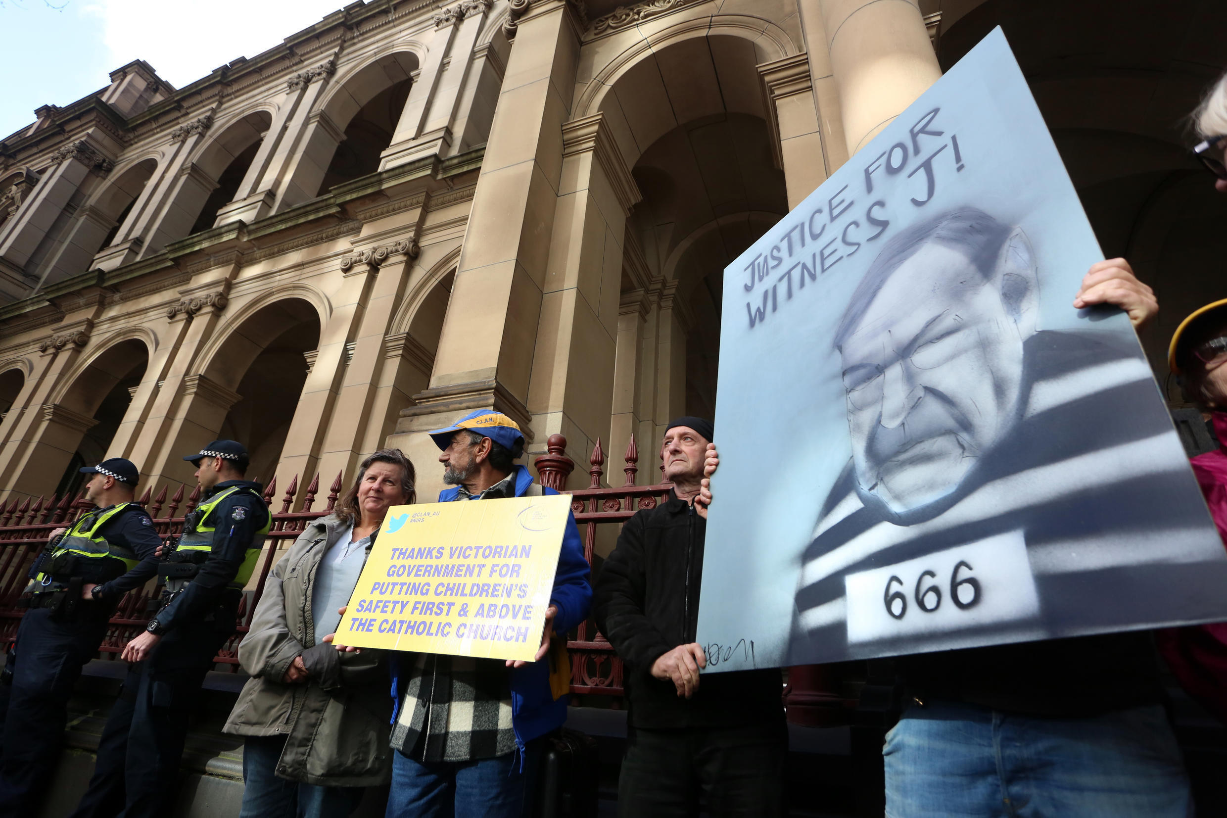 Protesters gather outside court as Australian Cardinal George Pell is escorted into the Supreme Court of Victoria in Melbourne last year