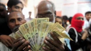 Un homme tient des billets de 500 et 1 000 roupies alors qu'il fait la queue, comme de nombreux indiens, le 10 novembre 2016, pour les changer contre de nouvelles coupures