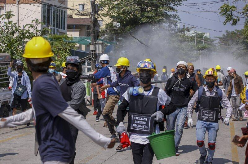 Anti-coup protesters retreat from the front line after unloading fire extinguishers at a line of riot police in Rangoon, Myanmar, Wednesday, March 10, 2021.
