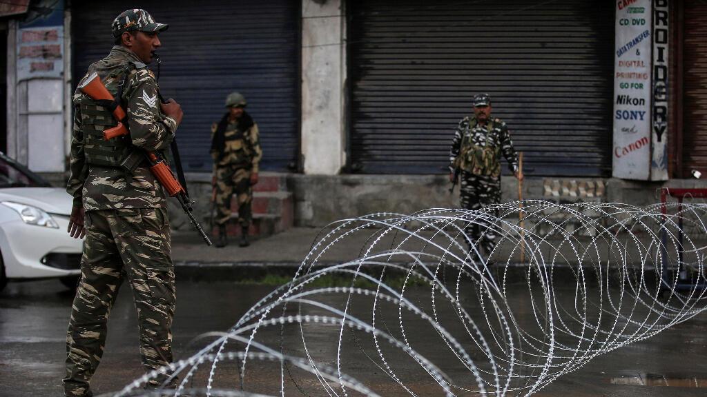 Personal de las fuerzas de seguridad indias en guardia junto al cable de la concertina tendido a través de una carretera durante las restricciones.