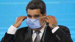 El presidente Nicolás Maduro se quita el tapaboca para participar de una rueda de prensa en Caracas el 17 de febrero