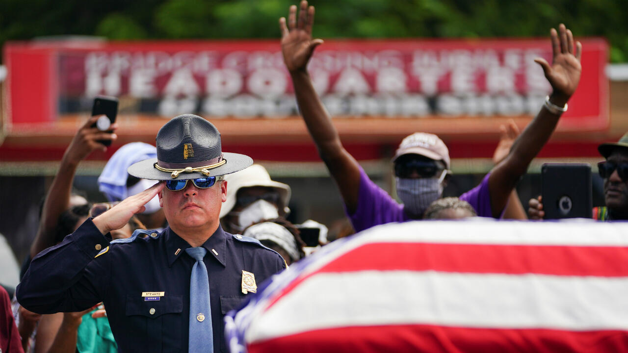 An Alabama State Trooper salutes the casket carrying the late US Congressman John Lewis after it was carried across the Edmund Pettus Bridge in a horse-drawn carriage in Selma, Alabama, on July 26, 2020.