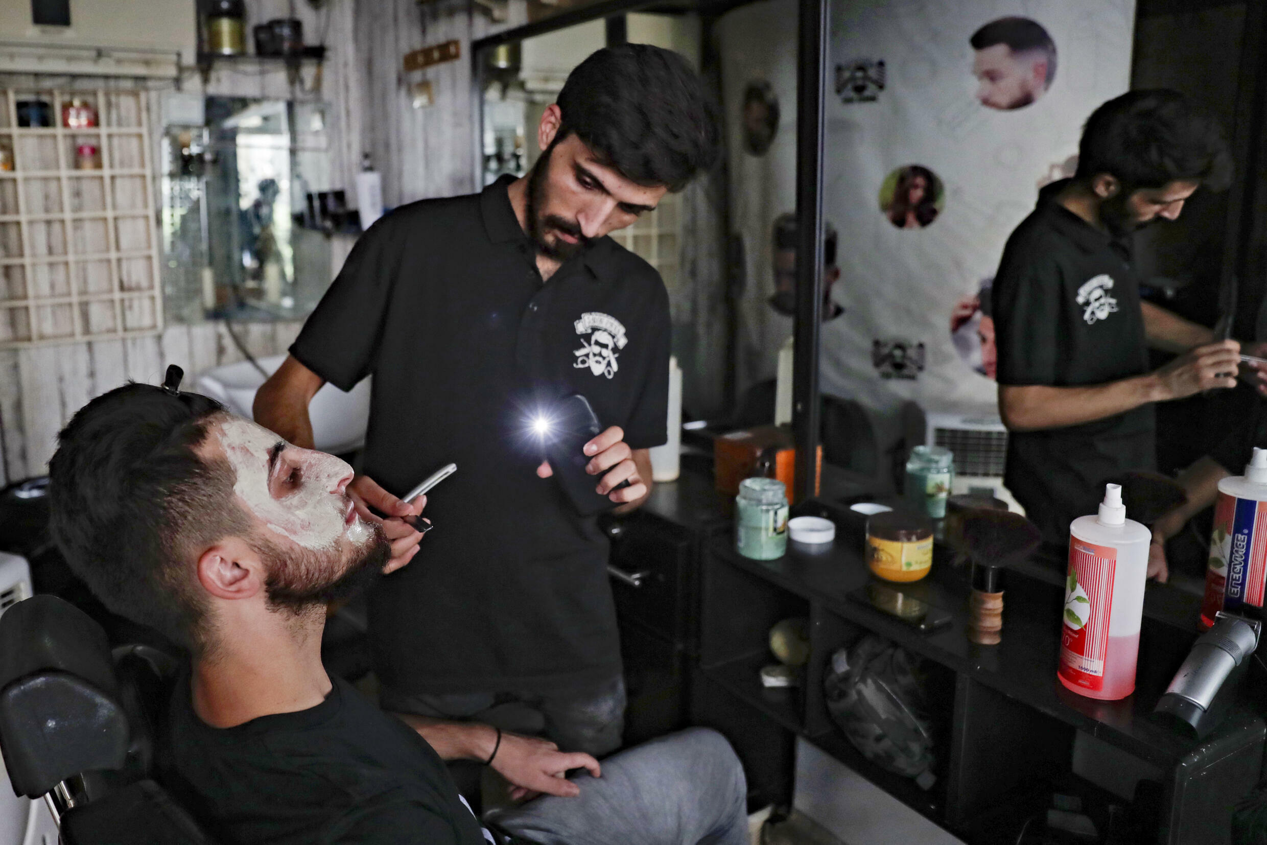A barber uses the flashlight on his phone as he shaves a customer due to the power outages while others have moved their chairs onto the pavement to get direct daylight