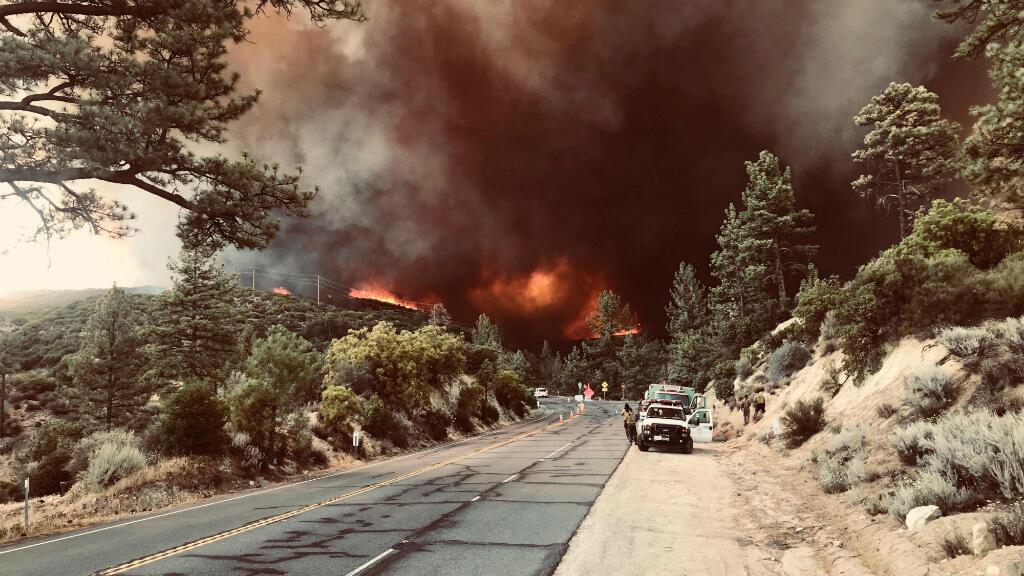 Bomberos observan el humo provocado un incendio cerca de Idyllwild, California, el 27 de julio de 2018.