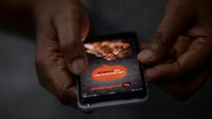 A woman signs in to get access to the Black & Black social network app in Rio de Janeiro, Brazil
