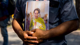 A protester holds an image of Aung San Suu Kyi outside the United Nations building in Bangkok on February 3, 2021.