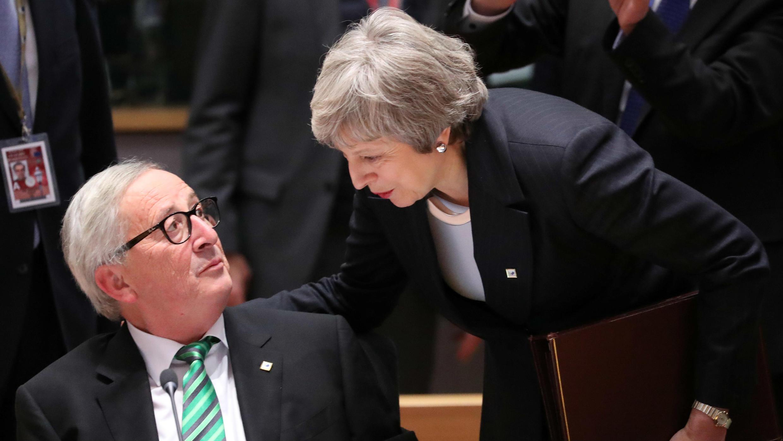 El presidente de la Comisión Europea, Jean-Claude Juncker, y la primera ministra británica, Theresa May, dialogan en la cumbre de líderes de la Unión Europea en Bruselas, el 13 de diciembre de 2018.