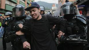Un joven es llevado por dos agentes antidisturbios durante una manifestación en Bogotá, Colombia. 21 de febrero de 2020.