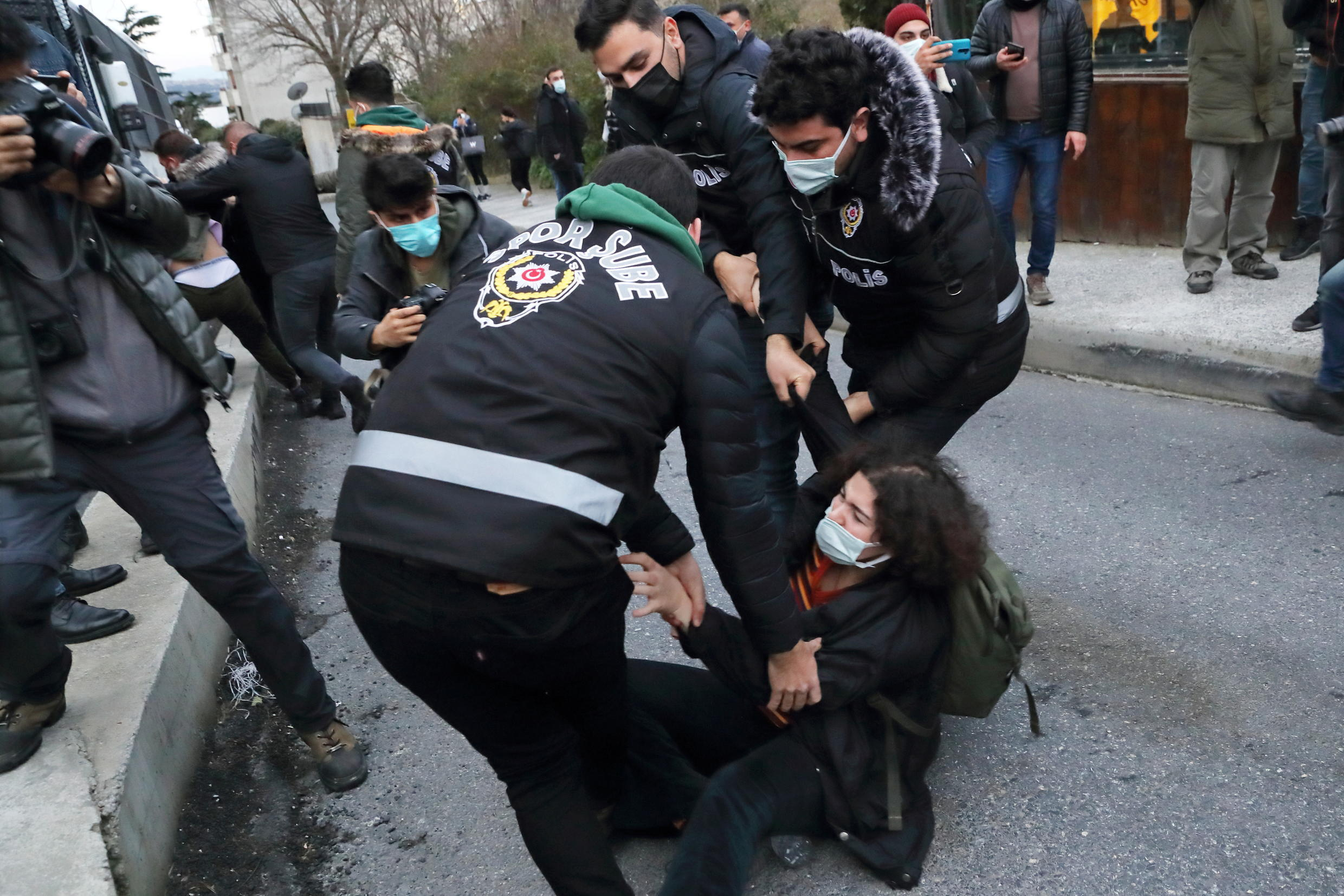 A woman scuffles with police officers as she waits in front of the Bogazici University in solidarity with students inside the campus who are protesting against the new rector and the arrest of two students, in Istanbul, Turkey February 1, 2021.