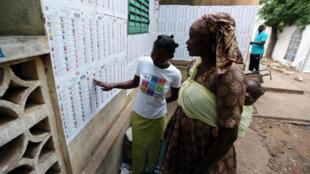 Un par de ciudadanas mientras buscaban sus nombres entre las listas electorales ubicadas en un punto de votación de Bamako, Mali, el 28 de julio de 2018.