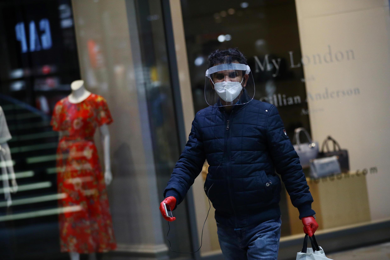 رجل يرتدي كمامة واقية أثناء سيره في الشارع - بريطانيا