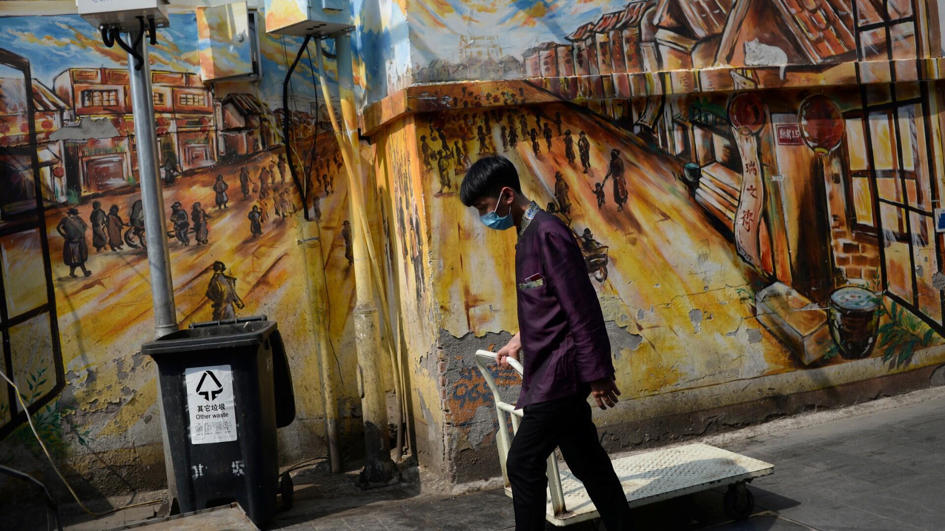Un trabajador que usa una máscara facial pasa un carro por una pared pintada cerca de la calle Qianmen, en el primer día de las vacaciones de cinco días del Día del Trabajo después del brote de la enfermedad por coronavirus (COVID-19), en Beijing, China, el 1 de mayo de 2020.