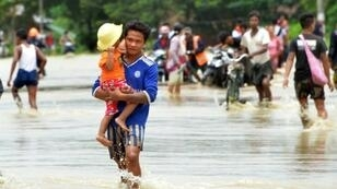 Residents negotiate a flooded road after waters breached the Swar Chaung dam