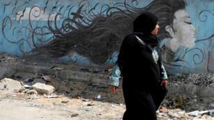 """Una mujer pasa junto a un mural que representa un mensaje de acoso antisexual y lee """"La mujer es libre"""" en una carretera en El Cairo, Egipto, el 3 de septiembre de 2018."""