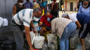 Colecta de agua de un surtidor público en Caracas, el 21 de marzo de 2020