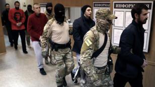 Los 24 marineros ucranianos que fueron acusados en Rusia de violar la frontera en un incidente naval en el mar Negro, mientras eran escoltados a su llegada al tribunal de Lefórtovo en Moscú, Rusia, el 15 de enero de 2019.