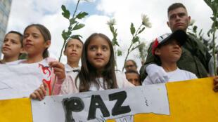 """Las personas participan en una marcha contra la violencia, después de la explosión de un coche bomba en Bogotá, Colombia, el 20 de enero de 2019. El cartel dice: """"Paz""""."""