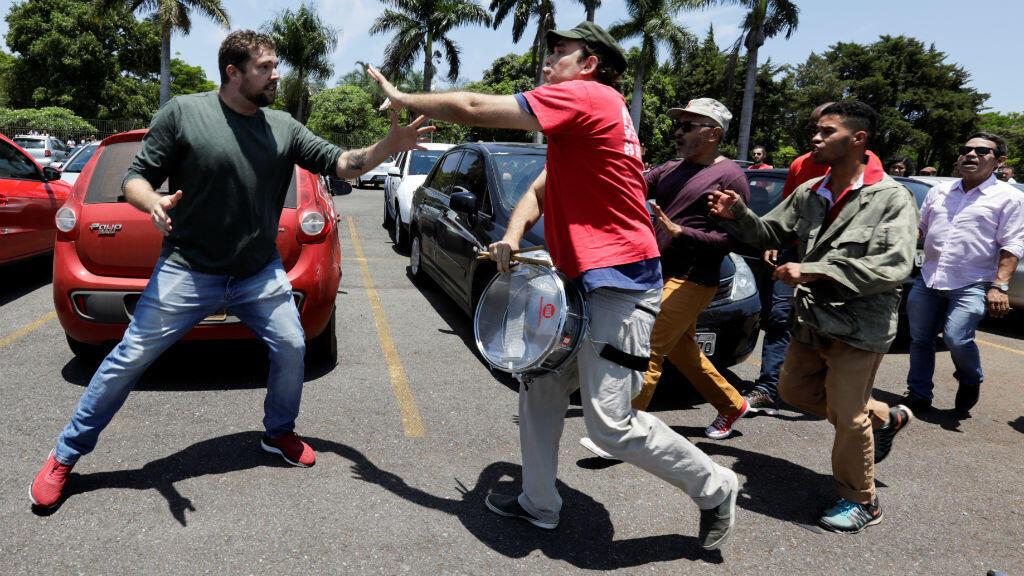 Un simpatizante del presidente de Venezuela, Nicolás Maduro, pelea con uno del líder opositor Juan Guaidó frente a la embajada de Venezuela en Brasilia, Brasil, el 13 de noviembre de 2019.