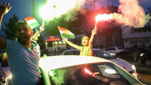 A supporter of pro-Kurdish Peoples' Democratic Party (HDP) waves a Kurdish flag as she celebrates in the streets the first results of the legislative election, in Diyarbakir on June 7, 2015. (Bulent Kilic, AFP)