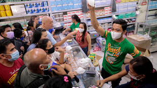 A vendor shows the only type of face mask they have available as people scramble to buy masks in a medical supply store after the Philippine government confirmed the first coronavirus death in Manila, Philippines, January 31, 2020.