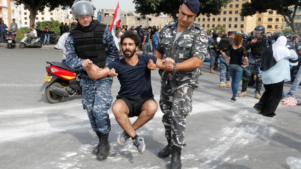 Des policiers libanais déplacent un protestataire participant au blocage d'une grande artère lors des manifestations antigouvernementales, à Beyrouth, le 26octobre2019.