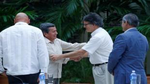 El jefe negociador del ELN, Pablo Beltrán, y el jefe negociador del Gobierno colombiano, Gustavo Bell, se dan un apretón de manos durante una sesión del proceso de paz en La Habana, Cuba, el 10 de mayo de 2018.